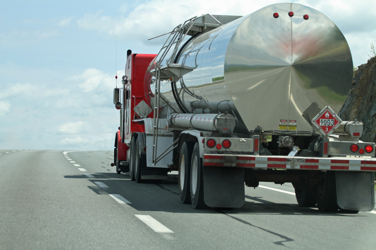 Rear quarter view of a semi tanker truck on a highway hauling a flammable/combustable liquid. Some motion blur with focus on cab. Note reflection of highway on rear of tank.